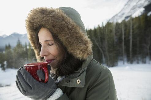 Woman in fur hood enjoying hot cocoa outdoors - HEROF09923