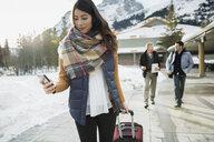 Woman pulling suitcase on sidewalk below mountains - HEROF09935