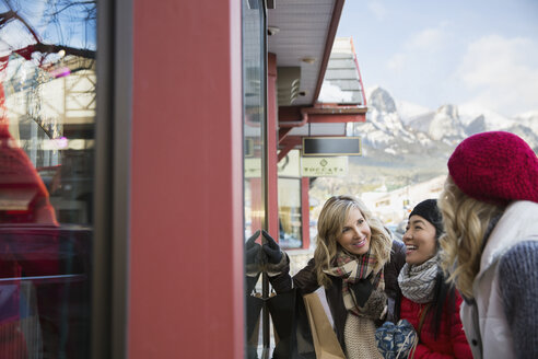 Women in warm clothing window shopping at storefront - HEROF09950