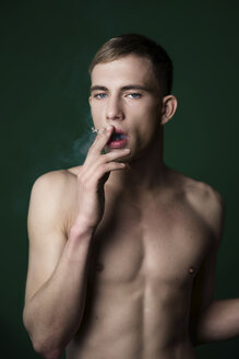 Portrait of self-confident nude young man smoking a cigarette in studio - VWF00060