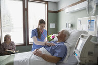 Nurse using stethoscope on patient in hospital room - HEROF10001