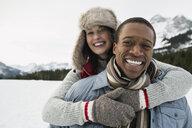 Portrait of hugging couple in snowy field - HEROF10148