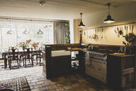 Interior view of kitchen with stone tile floor, range cooker and butler's sink, open plan to conservatory with antique wooden dining table and chairs. - MINF10192
