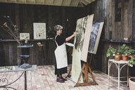 Senior woman wearing glasses, black top and white apron standing in studio, working on painting of trees in forest. - MINF10207