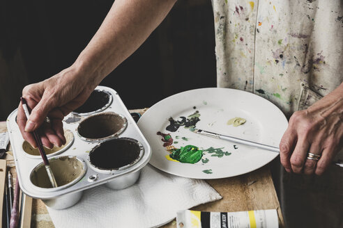 High angle close up of artist mixing green and brown colours on white plate. - MINF10210