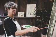 Senior woman wearing glasses, black top and white apron standing in studio, working on painting of trees in forest. - MINF10219