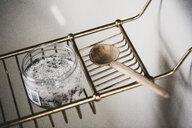 High angle close up of jar of bath salts and wooden spoon on brass bath caddy. - MINF10231
