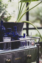 Close up of clear and blue glass jars and bottles on vintage metal table with drawer. - MINF10279