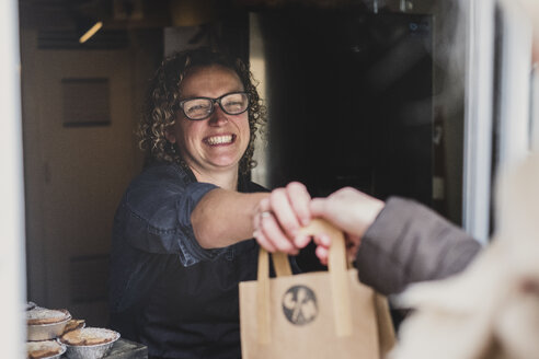 Smiling woman wearing glasses handing  brown paper shopping bag through window of bakery. - MINF10306