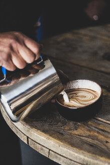Close up of barista pouring milk from jug into cappuccino mug, creating foam pattern. - MINF10324