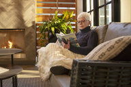 Senior woman relaxing, reading book on living room sofa next to fireplace - HEROF10193