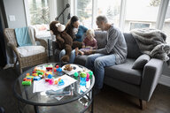 Grandparents and toddler granddaughter using digital tablet on living room sofa - HEROF10255