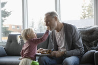 Cute granddaughter feeding grandfather muffin on living room sofa - HEROF10258
