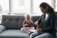 Playful grandmother tickling granddaughter s toes on living room sofa - HEROF10264