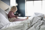 Cute toddler girl using digital tablet on bed - HEROF10297