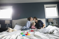 Affectionate couple with toddler daughter kissing on bed - HEROF10300