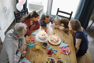 Multi-generation family celebrating toddler girl s birthday at dining table - HEROF10327