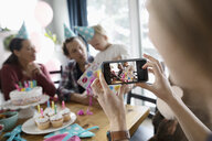 Woman with camera phone photographing toddler daughter opening birthday gift - HEROF10330
