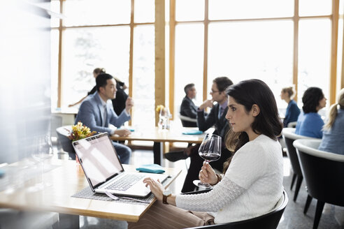 Businesswoman drinking red wine and working at laptop in restaurant - HEROF10348