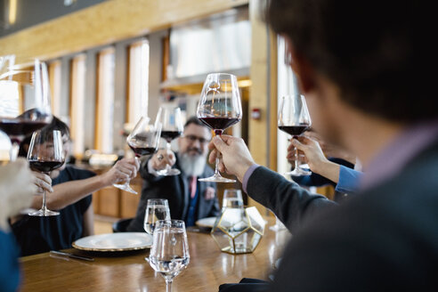 Business people toasting red wine glasses at restaurant table - HEROF10363