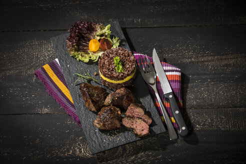 Kangaroo steak with red rice and mango on slate plate - MAEF12780