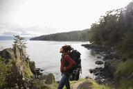 Man backpacking on cliff overlooking ocean - HEROF10398