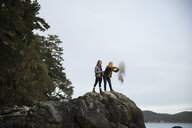 Mother and daughter spreading ashes on rocks - HEROF10407