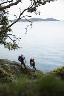 Mother and daughter backpacking on cliff overlooking ocean - HEROF10410
