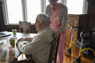 Home caregiver using stethoscope on senior man at dining table - HEROF10434