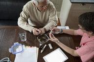 Home caregiver explaining medicinal marijuana to senior man - HEROF10437