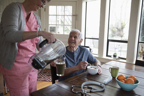 Home caregiver pouring green smoothie for senior man at kitchen table - HEROF10443