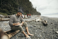 Man enjoying weekend surfing getaway, writing in journal on rugged beach - HEROF10488
