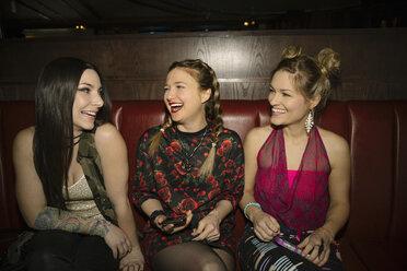 Happy female millennial friends laughing in nightclub - HEROF10509