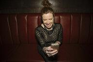 Laughing, happy female millennial taking selfie in nightclub - HEROF10512
