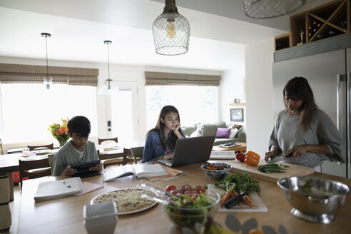 Mother cooking while tween daughter and son do homework in kitchen - HEROF10542