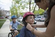 Mother fastening bike helmet on son on neighborhood sidewalk - HEROF10584