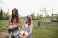 Mother and daughter with picnic basket and soccer ball in park - HEROF10593