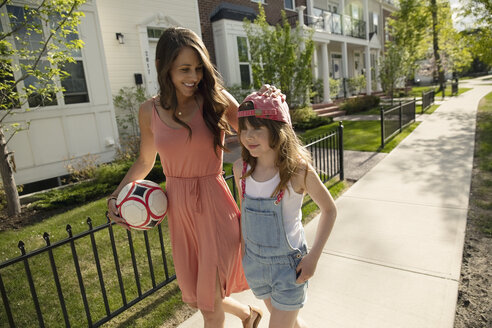 Mother and daughter with soccer ball walking on sunny neighborhood sidewalk - HEROF10596