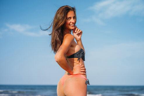Portrait of smiling young woman wearing tanga bikini on the beach - OCMF00234