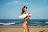 Portrait of happy young woman wearing bikini on the beach - OCMF00237