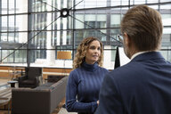 Businesswoman talking with businessman in office lobby - HEROF10612