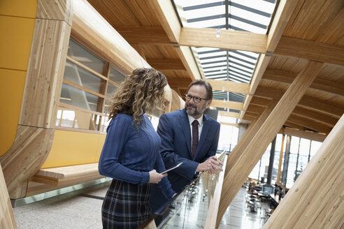 Business people with digital tablet talking in modern office corridor - HEROF10615