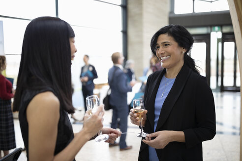 Smiling businesswomen networking, drinking champagne at conference happy hour - HEROF10645