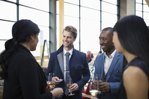 Smiling business people networking, drinking champagne at happy hour - HEROF10651