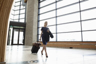 Businesswoman with smart phone pulling suitcase in airport - HEROF10687