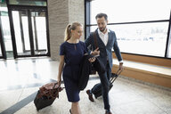 Businessman and businesswoman with suitcases talking in airport - HEROF10690