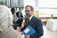 Smiling businessman networking at conference - HEROF10732