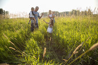 Young family in sunny, rural field - HEROF10759