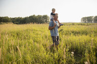 Father carrying son on shoulders in sunny, rural field - HEROF10762