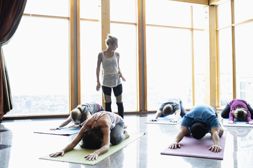 Female instructor leading yoga class practicing childs pose in studio - HEROF10876
